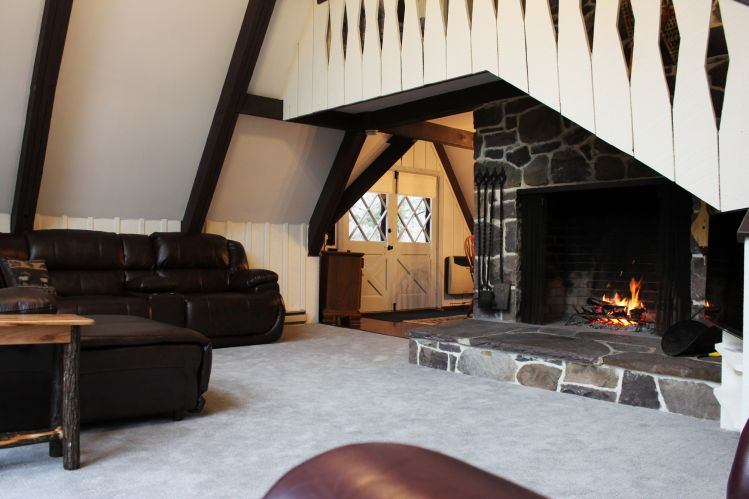 Living Room with vaulted ceilings leather power sectional and huge fireplace